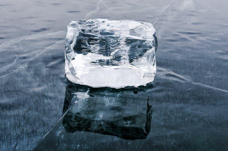 Singolo cubetto di ghiaccio con la riflessione sulla superficie del lago fotografie stock libere da diritti
