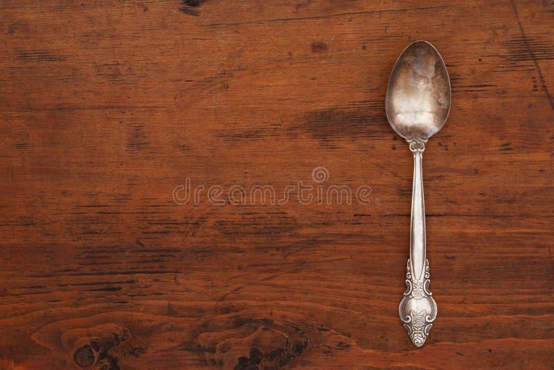 Singolo cucchiaio d'argento antico su una tavola di legno vuota con uno spazio della copia immagini stock libere da diritti