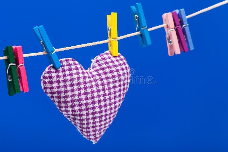 Singolo cuore sul clothesline con i clothespins fotografie stock