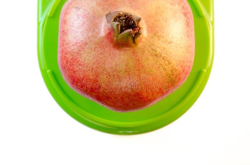 Singolo grande melograno rosso fresco sulla scala complementare verde della cucina isolata su fondo bianco, vista superiore fotografia stock libera da diritti