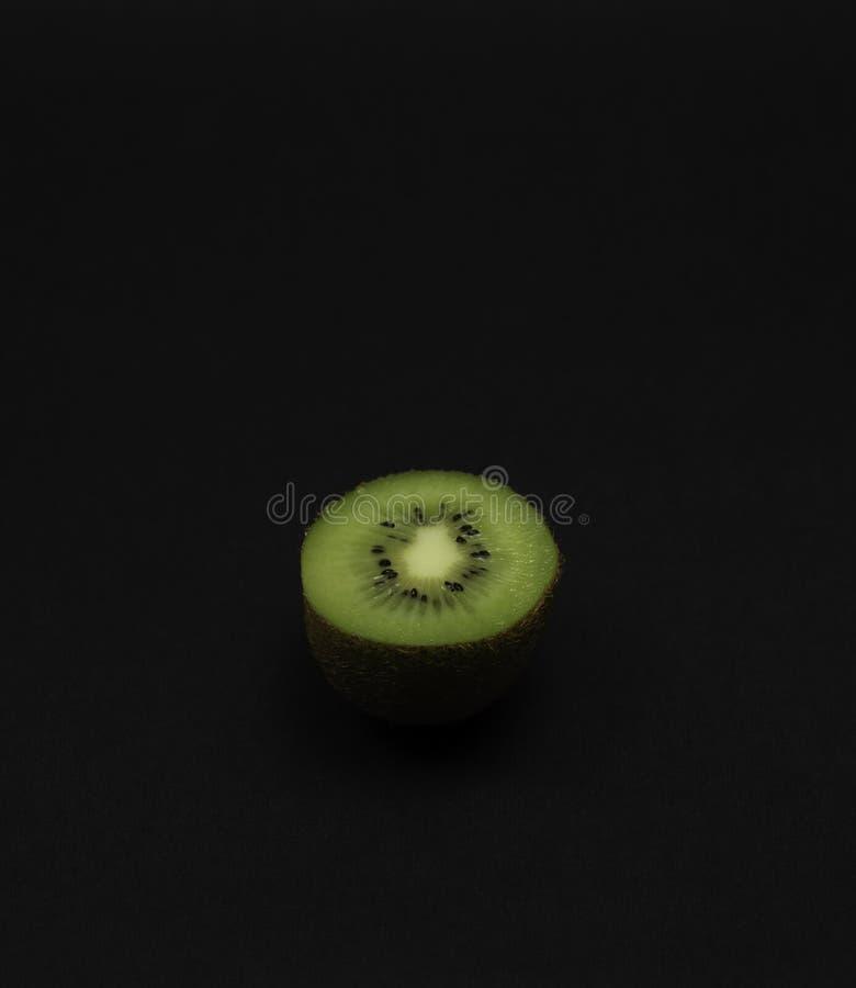 Singolo kiwi tagliato su fondo scuro immagine stock libera da diritti