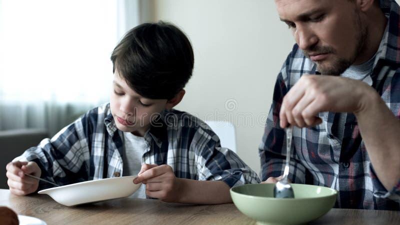 Singolo padre serio e suo il figlio che mangiano i fiocchi di granturco nella mattina, povera prima colazione immagine stock libera da diritti