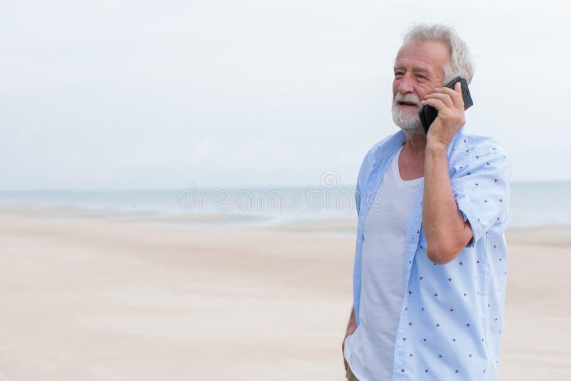 Singolo uomo senior che parla sulla chiamata durante la vacanza alla spiaggia del mare immagini stock