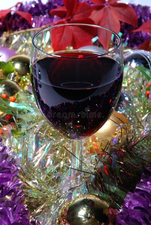 Singolo vetro di vino rosso su una priorità bassa di natale fotografie stock