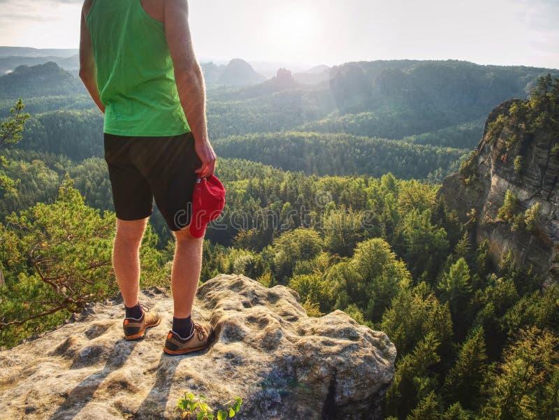 Singulet vert et garçon courageux de pantalon de noir dans les roches Vue étonnante images stock