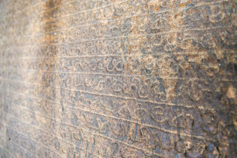 Sinhala inscription on the flat stone surface. With shallow depth of fields royalty free stock photo