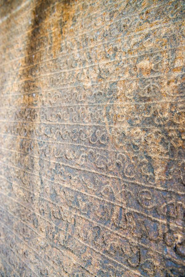 Sinhala inscription on the flat stone surface. With shallow depth of fields royalty free stock image
