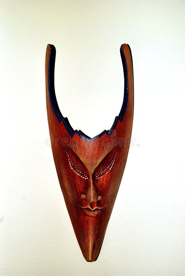 Sinister wooden mask with horns. Horned wooden mask with narrow chin and white dots on eyes stock images