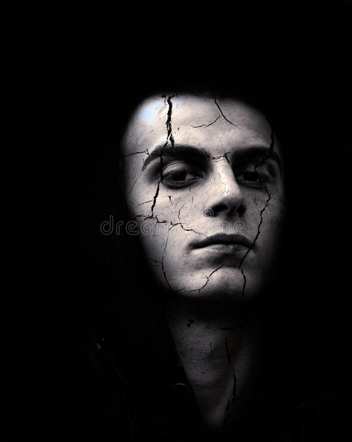 Sinister young man with cracked skin. Portrait of spooky looking man with cracked skin stock photo