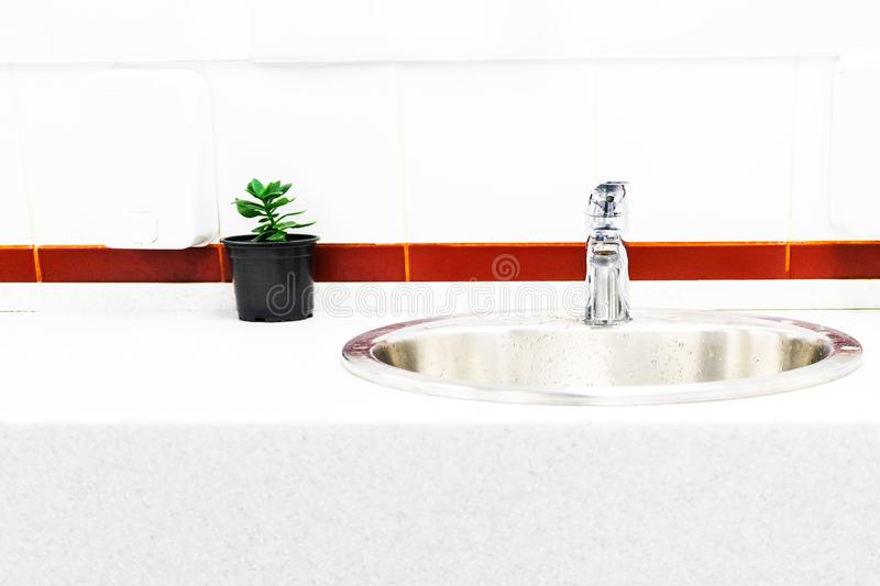 The sink in the bathroom on the background of bright tiles with a bright stripe, the design of a flower in a pot stock photo