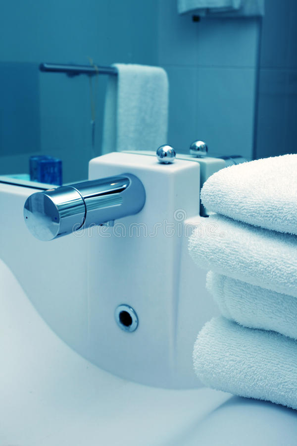 Sink in the hotel bathroom. Blue toned, focus on towels stock photography