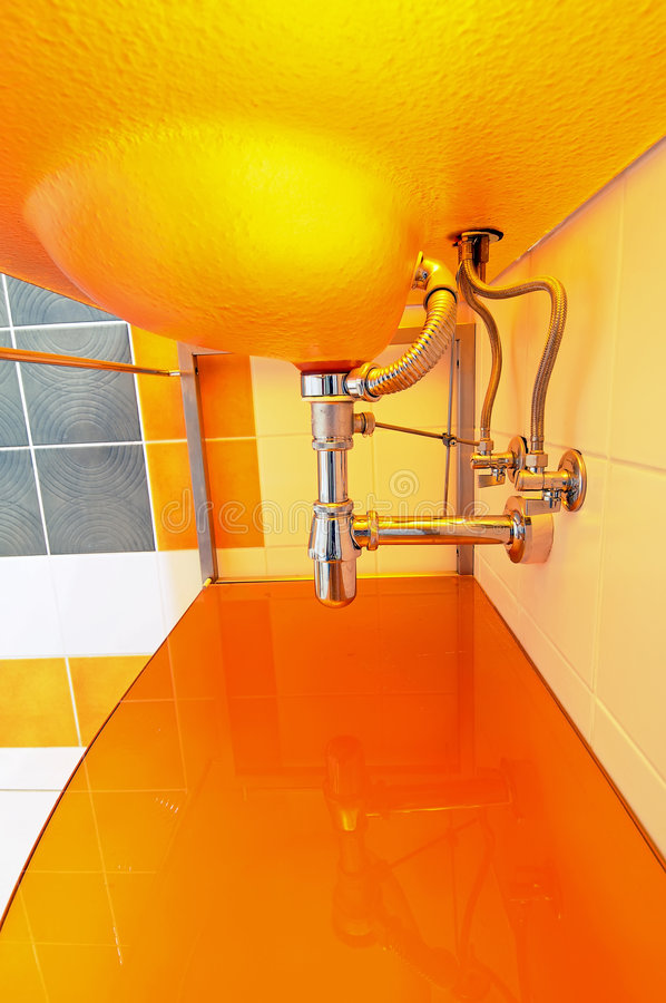 Sink pipes details. Details of the water pipes installation under modern orange sink royalty free stock image
