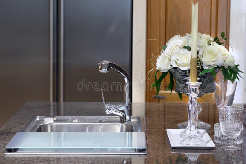 Sinken Sie mit Glas und Kerzenständer auf Marmortabelle in modernes kitche stockfoto