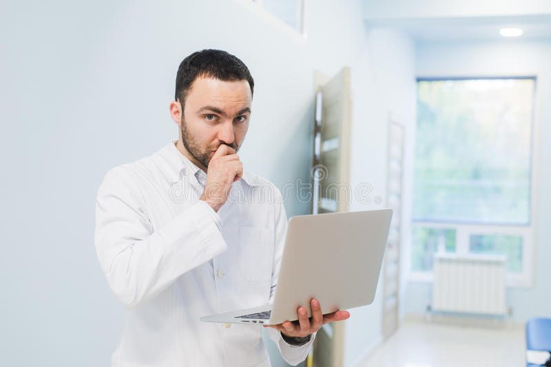 Sinnat lyckat doktorsanseende på hans kontor och användabärbar dator för hans arbete royaltyfri bild