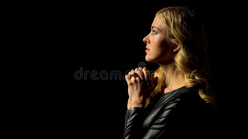 Sinner confession, young woman praying in darkness under heaven light, hope stock photography