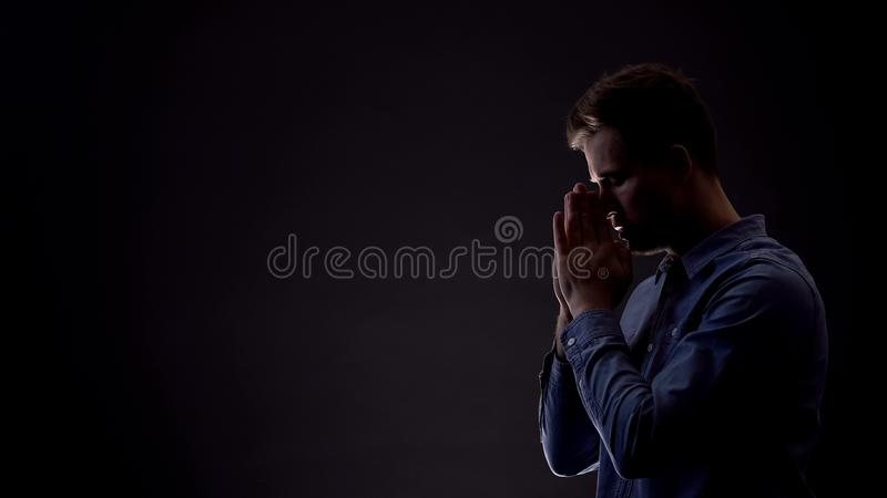 Sinner praying to God in dark room, asking for forgiveness, confession concept. Stock photo stock photo