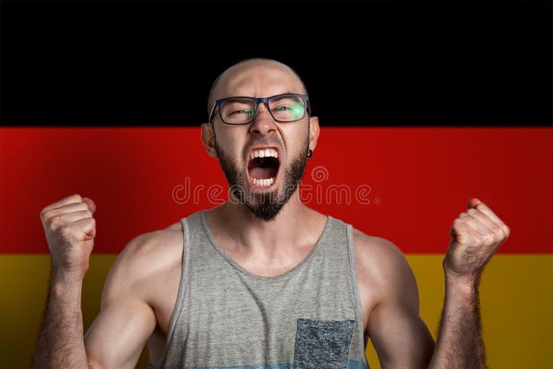 Sinnesrörelse av ilska och harm Mannen i exponeringsglas grep hårt om hans händer in i nävar och skrin I bakgrunden flaggan av royaltyfri fotografi