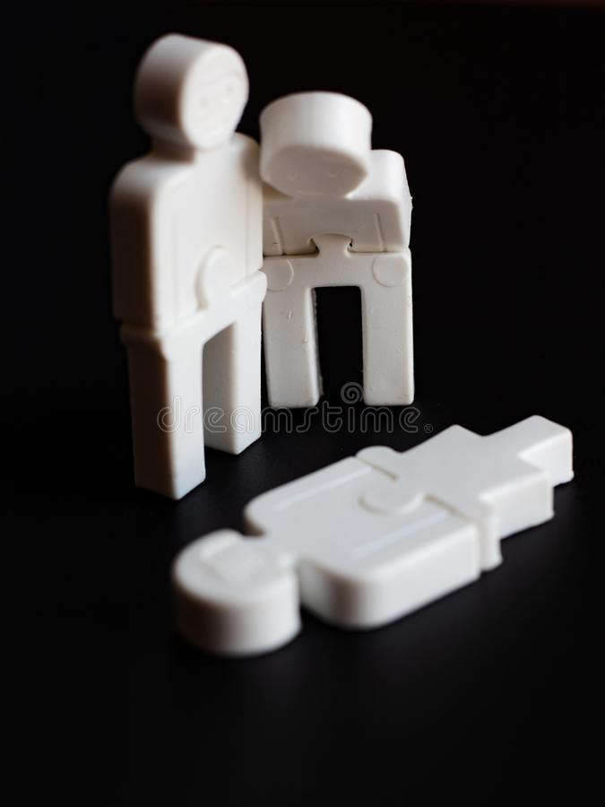 Sinnesrörelser av ångern mellan folk, begreppet av social service, små leksakmän på en mörk bakgrund arkivbild