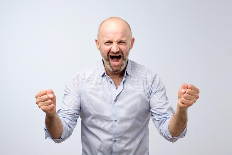 Sinnesrörelser av en televisionfan Ropa upp skrikiga hållande nävar för emotionell ilsken man Emotionell mogen framsida royaltyfria bilder