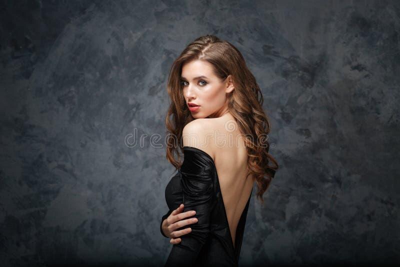 Sinnliche attraktive junge Frau im klassischen Kleid mit offenem Rücken lizenzfreies stockbild