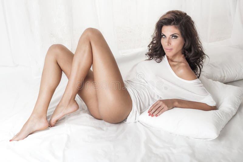 Sinnliche Brunettedame, die im Bett aufwirft stockbilder