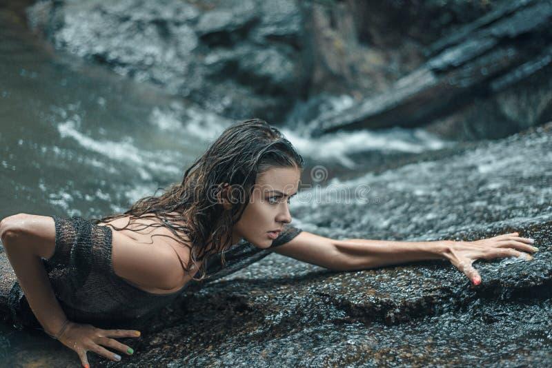 Sinnliche Dame, die auf den nassen Felsen wandert stockfotografie