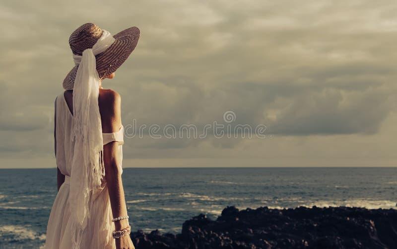 Sinnliche Dame am Strand im Hut- und Schmuckzubehör an den Sonnen stockbilder