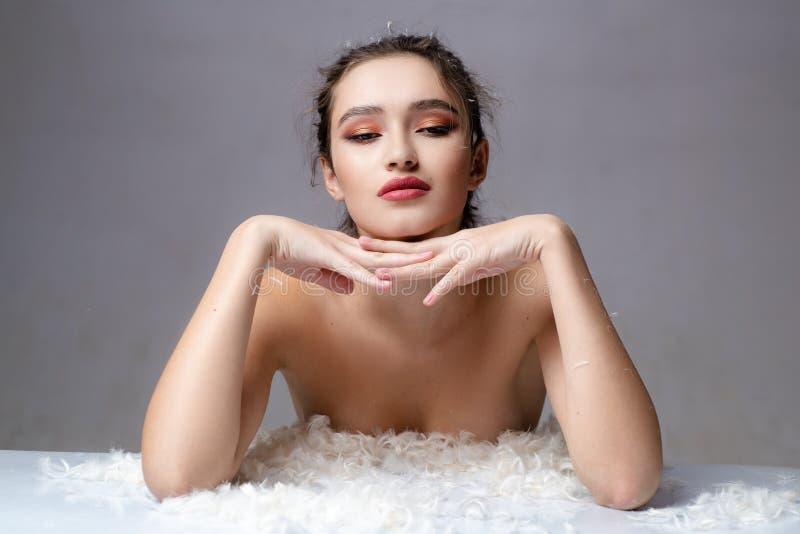 Sinnliche Frau in den weißen flaumigen Federn Guten Morgen S??e Tr?ume Weiche Haut Skincare Konzept Kosmetik- und Makeup stockfotos