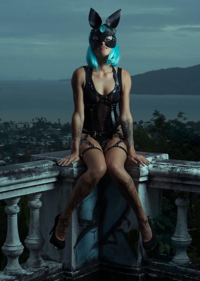 Sinnliche Frau in der blauen Perücke mit Ledergürteln und Kaninchenmaske stockbilder