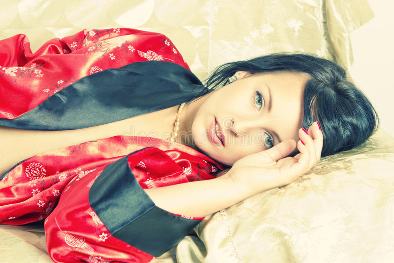 Sinnliche Frau, die auf Bett liegt stockbilder