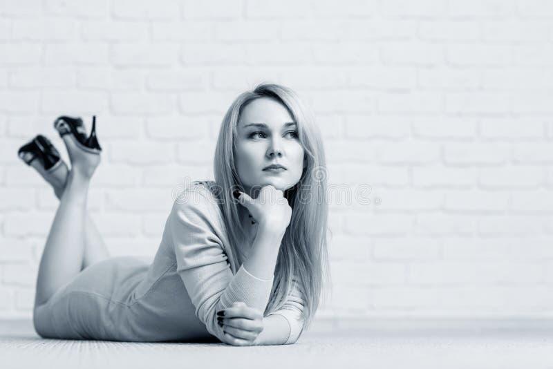 Sinnliche Frau, die auf Boden gegen weiße Backsteinmauer liegt lizenzfreies stockfoto