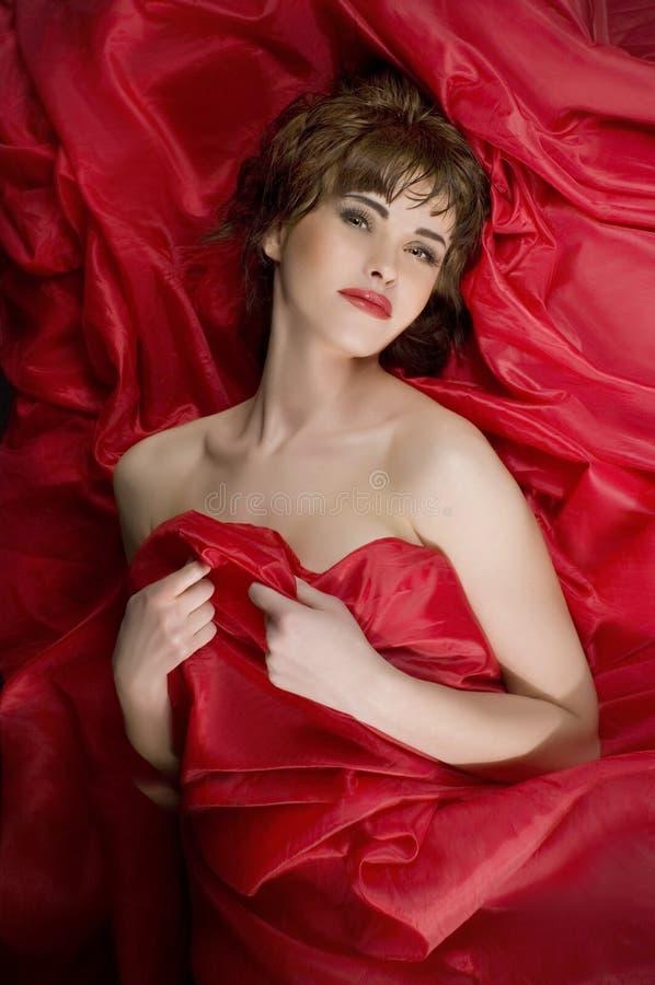 Sinnliche Frau, die auf rote Seide legt lizenzfreie stockbilder