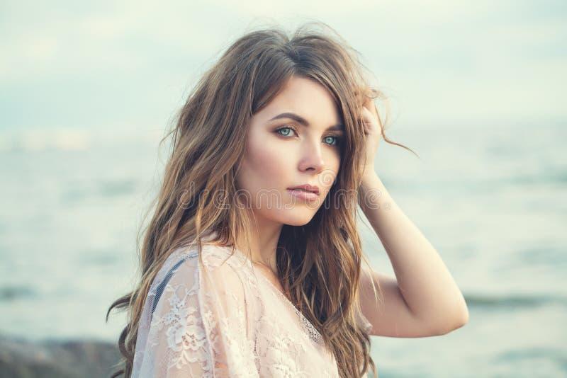 Sinnliche Frau im Freien Schönes vorbildliches Mädchen mit dem langen gelockten braunen Haar auf Ozeanhintergrund stockfoto