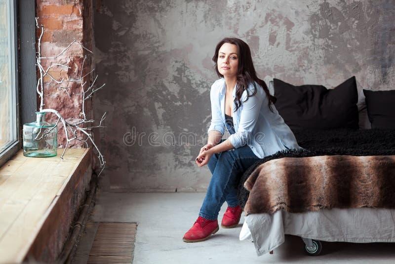 Download Sinnliche Frau Mit Dem Dunklen Haar Im Blauen Hemd Und In Den Jeans, Die Zu Hause Auf Einem Bett Sitzen Dachbodenartinnenraum Stockfoto - Bild von haupt, leben: 90230856