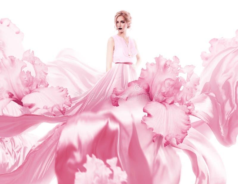 Sinnliche Frau mit dem Fliegen des rosa Kleides lizenzfreie stockbilder