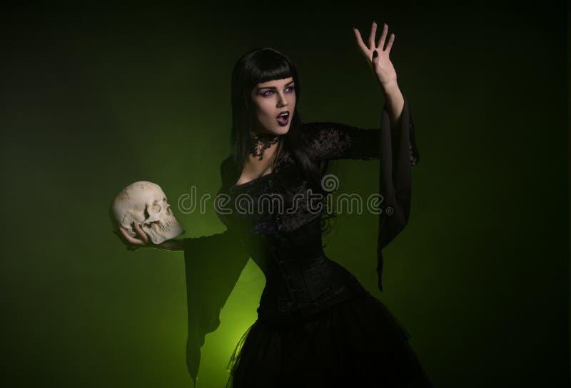 Sinnliche Hexe, die einen Schädel in ihrer Hand hält lizenzfreies stockfoto