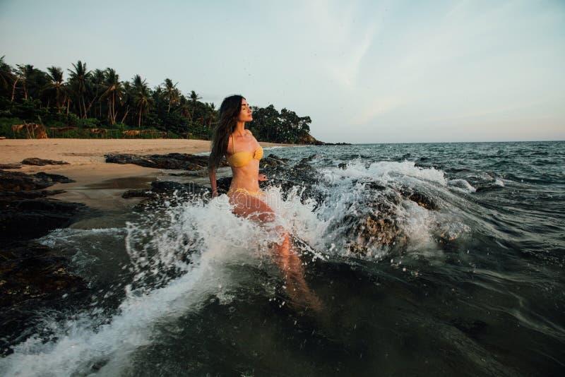 Sinnliche junge Brunetteschönheit, die gelben Badeanzug mit dem schönen Haar sitzt auf Stein am Strand trägt lizenzfreies stockfoto