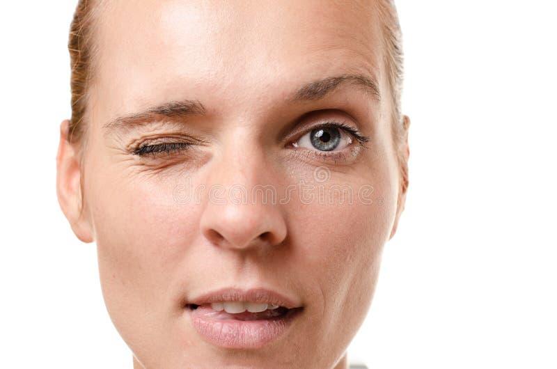 Sinnliche junge Frau, die an der Kamera blinzelt stockbild