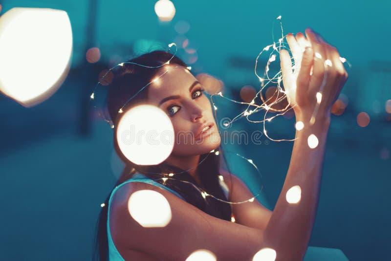 Sinnliche junge Frau, die mit den feenhaften Lichtern draußen schauen i spielt lizenzfreies stockfoto