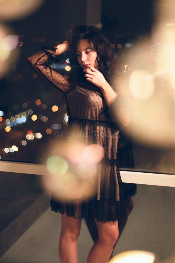 Sinnliche junge Frau im schwarzen Cocktailkleid vor Fenster nachts stockfotos