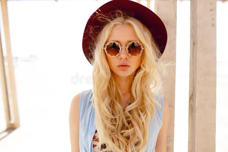 Sinnliche junge Frau mit den großen Lippen, tragend im stilvollen Hut und runden in der Sonnenbrille und draußen werfen auf stockfotografie