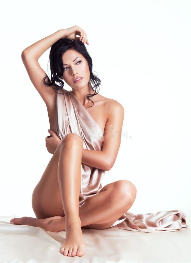 Sinnliche junge Frau mit schönem Körper in der beige Seide stockfotografie