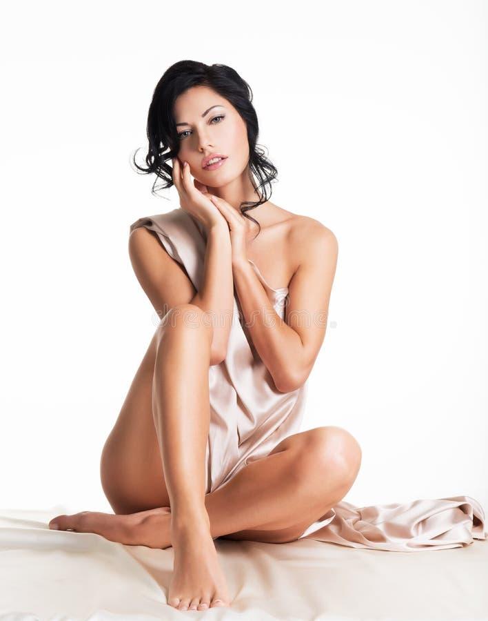 Sinnliche junge Frau mit schönem Körper in der beige Seide lizenzfreies stockbild