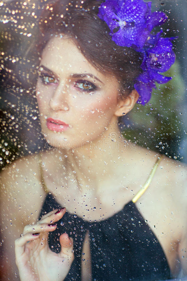 Sinnliche schöne Brunettefrau mit Blumen in ihrem Haar an stockfotografie