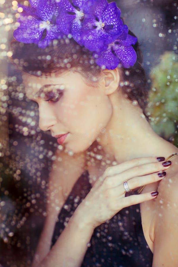 Sinnliche schöne Brunettefrau mit Blumen in ihrem Haar an lizenzfreie stockbilder