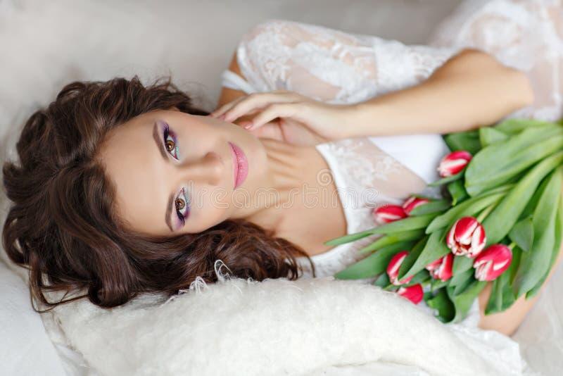 Sinnliche schöne und reizend Brunettefrau, die auf Bett und s liegt lizenzfreie stockfotos