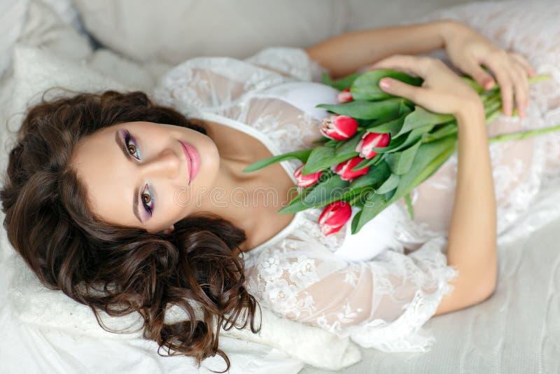 Sinnliche schöne und reizend Brunettefrau, die auf Bett und s liegt stockbild