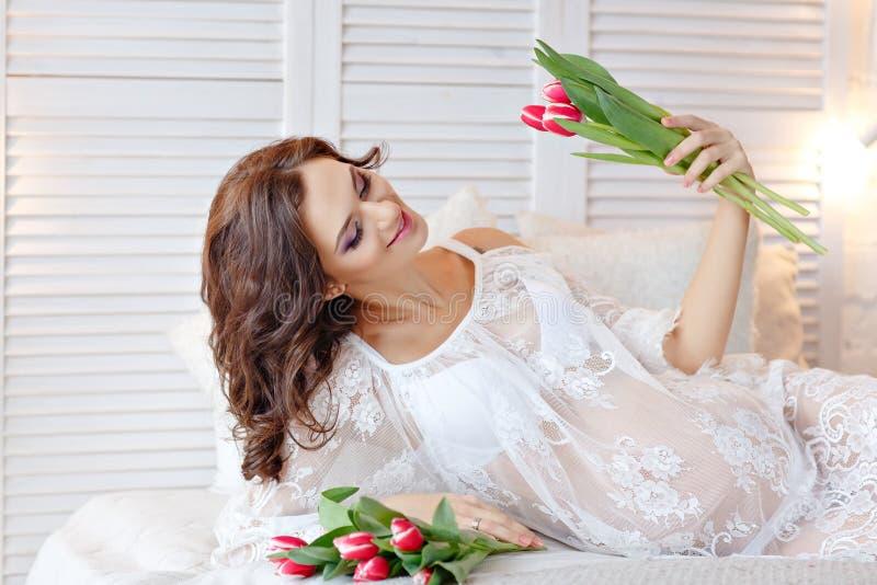 Sinnliche schwangere Frau des schönen und reizend Brunette, die an liegt lizenzfreies stockbild