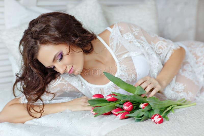 Sinnliche schwangere Frau des schönen und reizend Brunette, die an liegt stockfotos