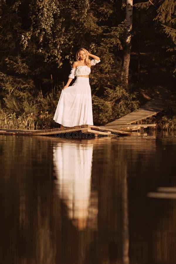 Sinnliche Stellung der jungen Frau auf hölzerner Plattform durch den See bei Sonnenuntergang oder Sonnenaufgang stockfoto